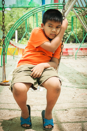 asian boy sad alone at playground Stock Photo
