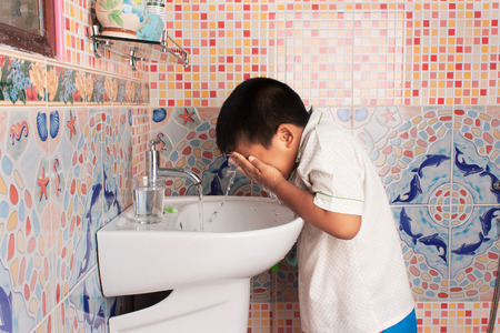 cleaning bathroom: little boy cleansing face in the bathroom
