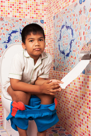 defecate: little asian boy defecate in toilet background
