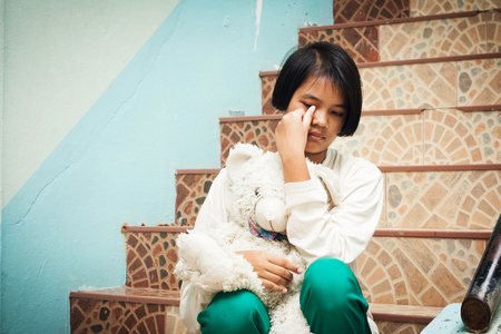 alone: girl sitting alone at staircase in the park Stock Photo