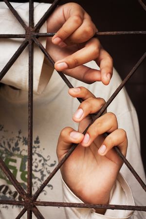 incarcerated: hand girl in jail bars Stock Photo