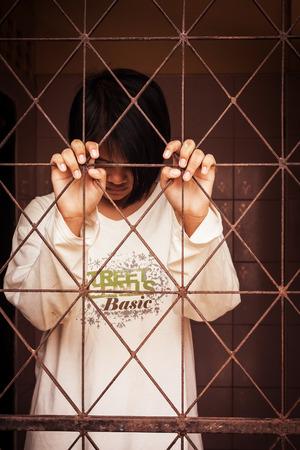 jail: girl standing  behind jail