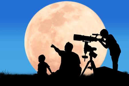 Silhouet van een kleine jongen die door een telescoop op de volle maanachtergrond kijkt