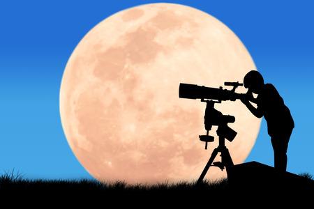 満月背景に望遠鏡を通して見る男の子のシルエット