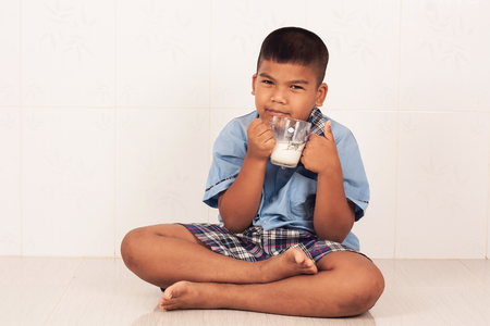 assent: school  boy drinking milk and concede