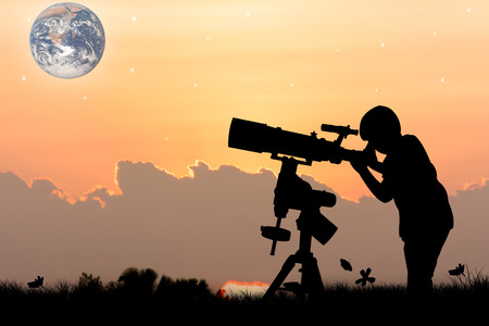 eyepiece: silhouette of little boy looking through a telescope at sunset  background