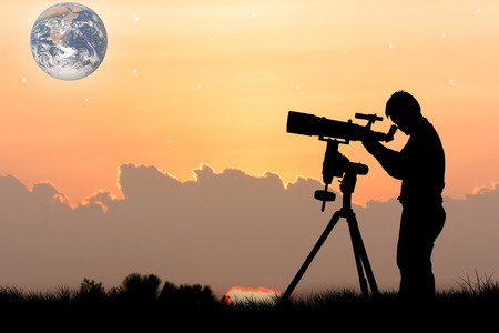 eyepiece: silhouette of young man looking through a telescope at sunset background,the backdrop of the planet earth. Elements of this image furnished by NASA.