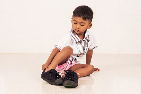 toddler boy: school boy wearing big shoe