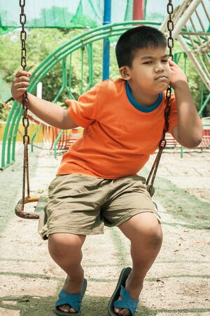 dismal: asian boy sad alone at playground Stock Photo