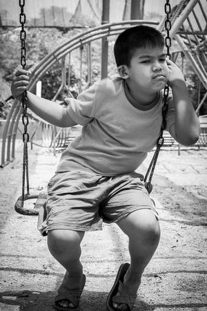 asian boy sad alone at playground blank and white tone