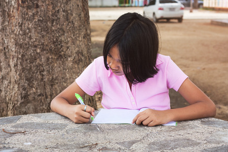 kids studying: cute girl writing book in the garden Stock Photo