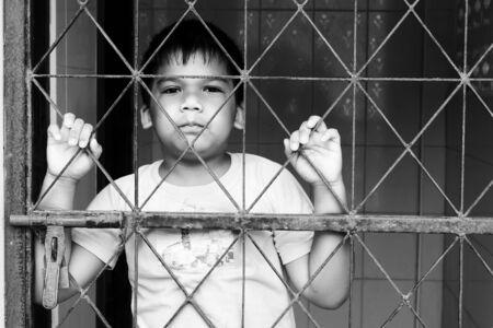 ni�os tristes: muchacho triste se coloca solamente detr�s de la c�rcel, negro y tono blanco
