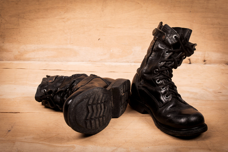 combat boots: old black combat boots on wooden background