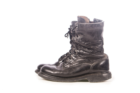 combat: old black combat boots on white background Stock Photo
