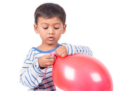 red white: happy cute little boy play with red balloon Stock Photo