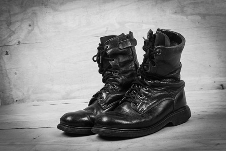 combat boots: old black combat boots on wooden background,black and white tone