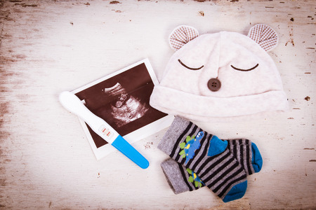 ultrasound with pregnancy test on wooden background Stockfoto