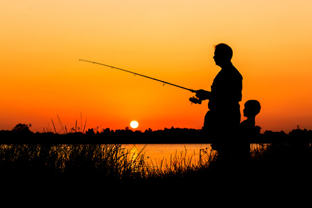 lake sunset: father and son fishing in the river sunset background