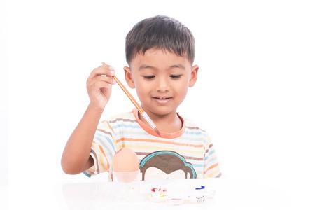 brush painting: ittle boy painting easter egg Stock Photo