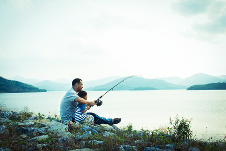fishing lake: son and dad fishing at dam,vintage tone