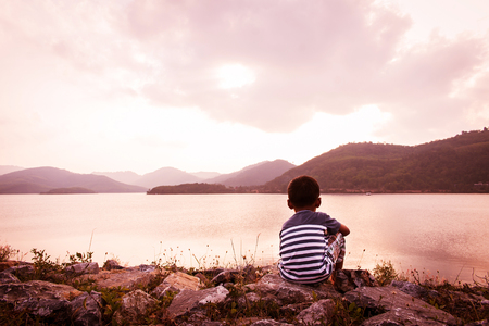 boy sitting: little boy sitting alone at dum in the evening Stock Photo