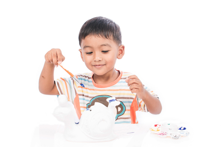 messily: cute little boy playing with paints Stock Photo