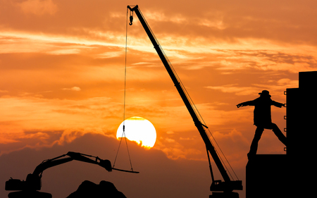 foreman: silhouette of construction foreman worker controlling the excavator and crane