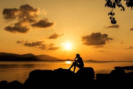mujer mirando el horizonte: hermosas mujeres que se sientan en el fondo de la playa puesta de sol
