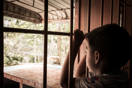 confined: little boy Hand in jail looking out the window