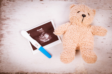 ultrasound with pregnancy test on wooden background Stock Photo
