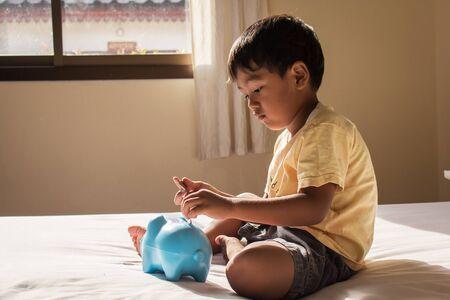 cute asian boy saving money in piggy bank Stock Photo