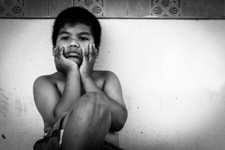 pauper: kid pauper sitting against the concrete wall,black and white tone