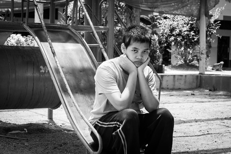 pauper: Girl pauper sitting alone at playground,black and white tone