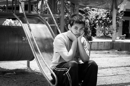 underprivileged: Girl pauper sitting alone at playground,black and white tone