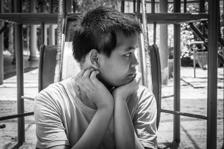 joyless: asian girl sitting alone at playground Stock Photo