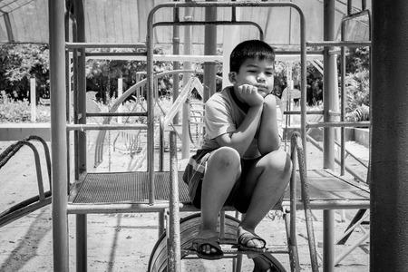 joyless: asian boy sitting alone at playground,black and white tone Stock Photo