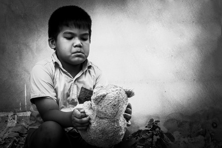 pauper: Kid pauper with old teddy bear sitting near the concrete wall,black and white tone Stock Photo