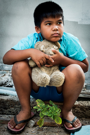 underprivileged: Boy poor with old teddy bear sitting on old wood pile