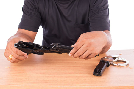 disassembled: Young man disassembled gun on table Stock Photo