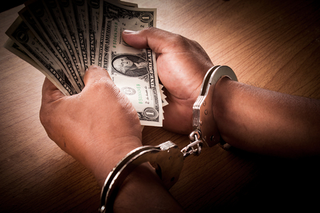 Hand young man in handcuffed hold money