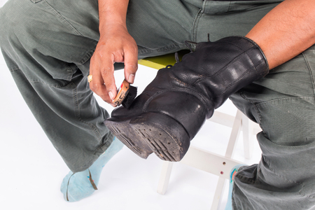foot ware: Man cleaning combat shoes Stock Photo