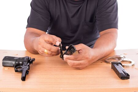 Young man disassembled gun on table Stock Photo