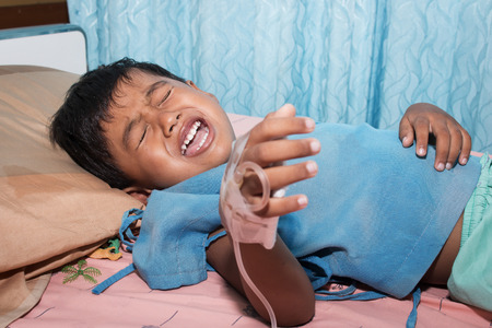 recuperation: Little boy sick and crying on patient bed Stock Photo