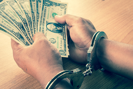 handcuffed: Hand young man in handcuffed hold money vintage tone