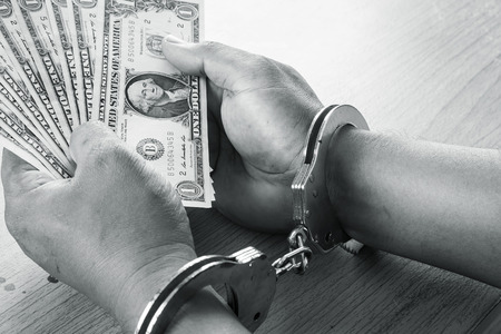 handcuffed: Hand young man in handcuffed hold money black and white  tone