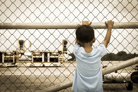 incarcerated: Behind of little boy sad standing alone