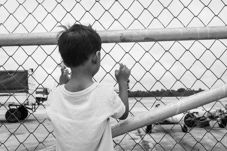 incarcerated: Behind of little boy sad standing alone ,black and white tone
