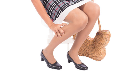 working woman holding her hurting ankle