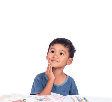 Cute little boy thinking while doing homework Stock Photo