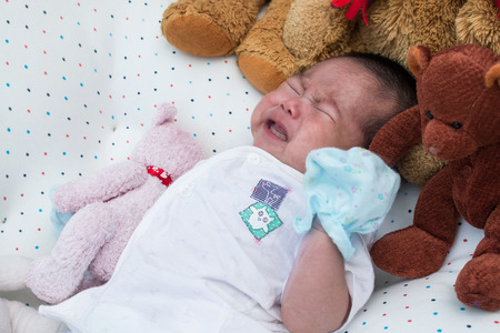 colic: Cute little newborn unsleep and crying on the bed Stock Photo